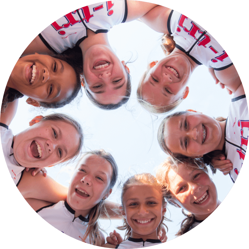 Camera looks up at a circle of 8 i-tri girls forming a ring with their heads and shoulders