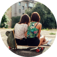 Two girls sit side-by-side on a longboard
