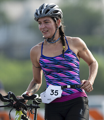 A participant in the i-tri triathlon with her bicycle